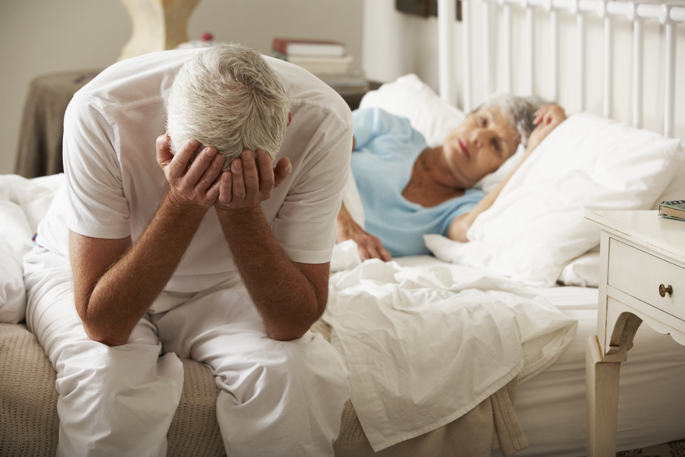 Worried Senior Man Sits On Bed next to Wife